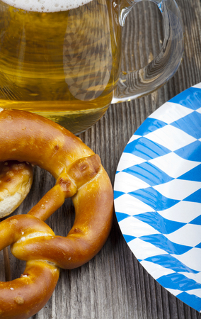 paper plates: Part of of a beer glass, pretzels and a Paper Plates with blue and white rhombuses on a rustic wooden table Stock Photo