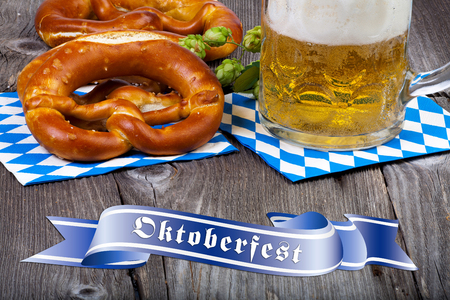 A beer mug and pretzels on napkins with blue and white rhombuses on a rustic wooden table at the bottom a blue banner with the words Oktoberfest photo