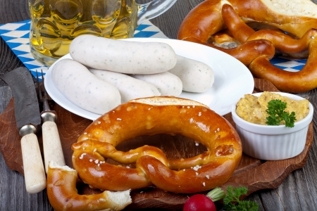 traditonal: Typical Bavarian Oktoberfest snack with white sausage, mustard, a glass of beer and pretzels on an old rustic wooden table