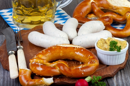 Typical Bavarian Oktoberfest snack with white sausage, mustard, a glass of beer and pretzels on an old rustic wooden table photo