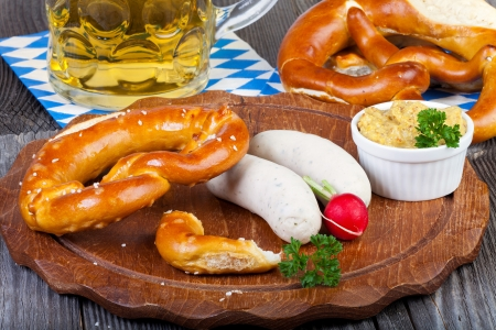 veal sausage: Round wooden cutting board with Veal sausage, pretzel, mustard and radish and a glass with beer on an old rustic wooden table Stock Photo