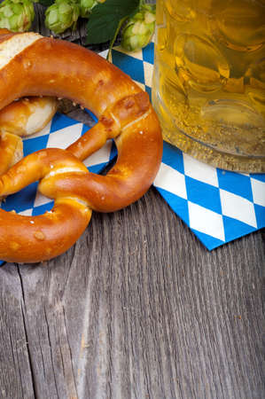 traditonal: A beer mug and pretzels on napkins with blue and white rhombuses on a rustic wooden table