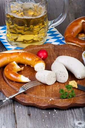 Round wooden cutting board with Veal sausage, pretzel, mustard and radish and a glass with beer on an old rustic wooden table photo