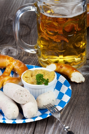 veal sausage: Typical Bavarian Oktoberfest meal with Veal sausage, mustard, pretzels and a cold beer on a rustic wooden table