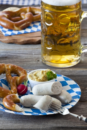 Oktoberfest meal with Veal sausage, mustard, pretzels and a cold beer on a rustic wooden table photo