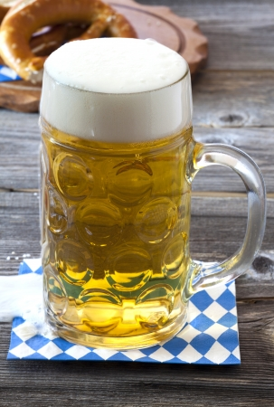 Large beer mug with beer on a napkin with blue and white rhombuses on a rustic wooden table in the background a wooden cutting board with pretzels photo