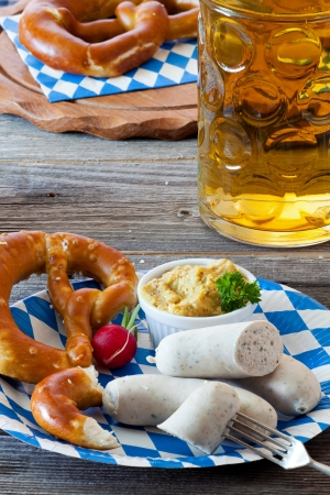 Blue-white paper plate with Veal sausage, pretzel, mustard and radish and a glass with beer on an old rustic wooden table photo
