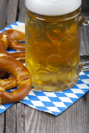 A beer mug and pretzels on napkins with blue and white rhombuses on a rustic wooden table photo