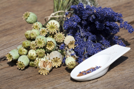 Summer crop of lavender, poppy capsules and poppy seeds in a small porcelain bowl on a rustic wooden table photo
