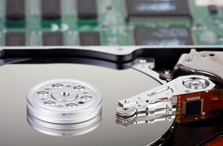 mass storage: Detailed Picture of an opened hard disk with a computer circuit board in the background Stock Photo