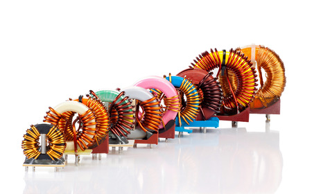 Selection of ten various Industrial Toroidal Choke Coils placed diagonally in a row isolated on White Background photo