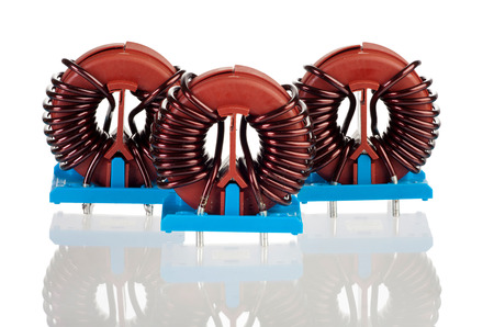 choke: Three Industrial Toroidal Choke Coil isolated and reflected on White Background Stock Photo