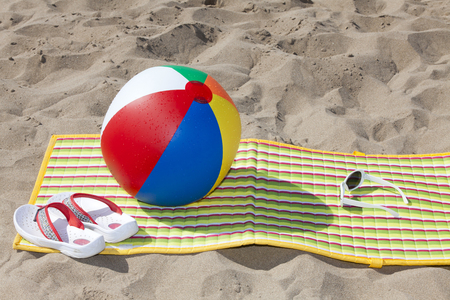 beach mat: Beach scene in the Summer with Flip-Flops, Beach Ball, Beach Mat, Sunglasses with Copy Space in upper part of image