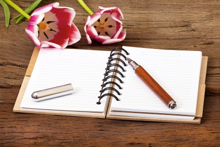 writable: Note Pad opened with writable page and a Pen on old wooden Background