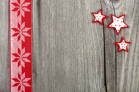 Christmas Card with Copy Space, red-white Fabric Ribbon and small wooden Stars on old wooden Board Stock Photo - 23483209