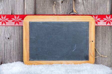Christmas Card with old Slate Chalkboard and Copy Space on a old wooden Board with red-white Fabric Ribbon Stock Photo - 23483211