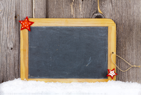 Christmas Card with old Slate Chalkboard and Copy Space on a old wooden Board with red wooden Stars Shape Stock Photo - 23483212