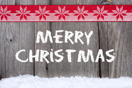 Christmas Greetings with Snow Script on old wooden Board with a red-white Fabric Ribbon Stock Photo - 23483213