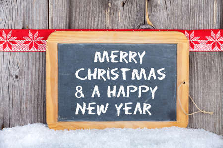 Christmas and a Happy New Year Greetings on old Slate Chalkboard Stock Photo - 23483214