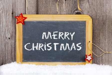 Christmas Greetings old Slate Chalkboard with Words  Merry Christmas  on old wooden Board Stock Photo - 23483225