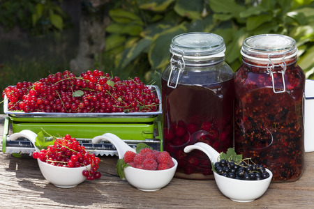 Fresh raspberries and black and red currants and each a glass jar with homemade blackcurrant liqueur and cherry liqueur on a wooden table in the garden