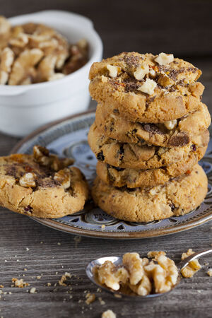 goods: Homemade Walnut Chili Cookies Stacked on a Plate on a old rustic Wooden Board