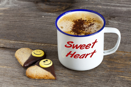 sweet heart: Enamel Mugs with hot Coffee and two Cookies in Heart Shape on a rustic wooden board with the Word  Sweet Heart  on the Mug
