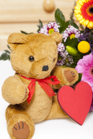 valentine s day teddy bear: Plush Teddy with red heart, in bouquet with copy space on the heart