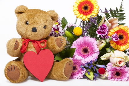 valentine s day teddy bear: Plush Teddy Greetings with a red heart and a colorful bouquet isolated on white Background