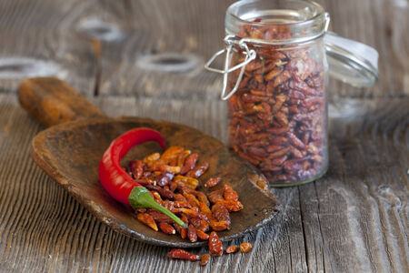 piri piri: Red chili pepper on a wooden scoop with dried chillies from a Storage Jar with copy space in upper left area of the image