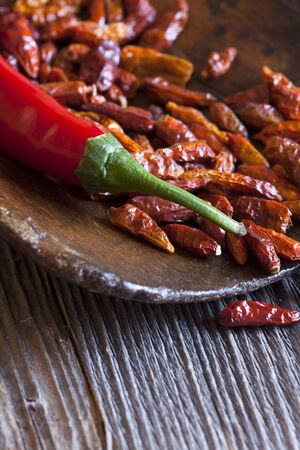 piri piri: Close-up of a red hot chili pepper on a wooden scoop with dried chili peppers and copy space in the lower area of the image