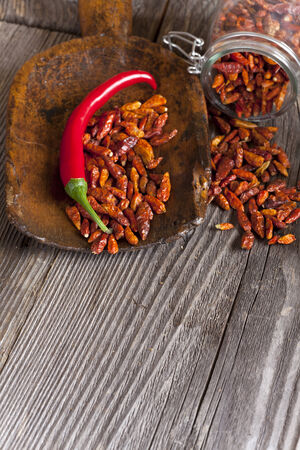 piri piri: Fresh and dried chili peppers on an old wooden scoop and a Storage Jar with copy space in the lower area of the image