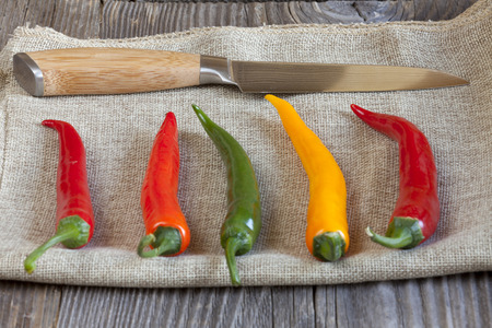 Various chili peppers on a jute fabric in the is a kitchen knife photo