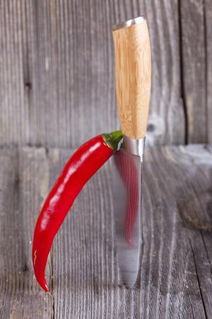 piri piri: Piri Piri chilli pepper stands ajar vertically on a kitchen knife with copy space in the upper area of the image
