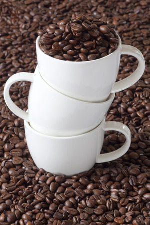 Three Coffee Cups stacked, one filled with Coffee Beans and two empty photo