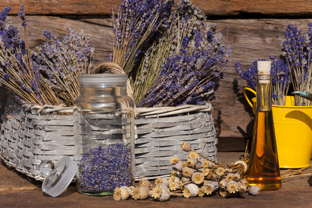 Dried lavender blossoms and poppy capsules on a table in front of a garden shed photo
