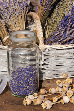 Storage jar dried lavender blossoms and poppy capsules on a table in front of a garden shed photo