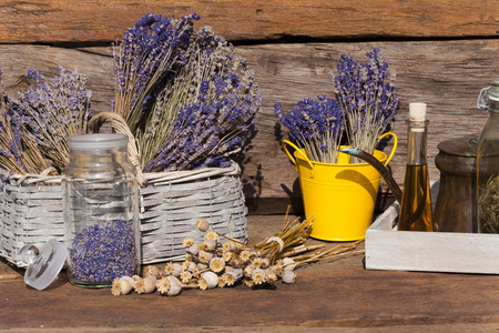 Summer crop of dried lavender, poppy seeds and poppy oil on a wooden table in front of a garden shed photo