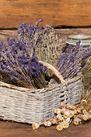 Basket filled with dried lavender bunches on a wooden table in front of a wooden hut photo
