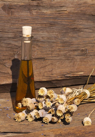 Summer harvest of dried poppy capsules and poppy oil on a wooden table in front of a garden shed photo