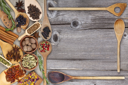 Spices and Herbs with wooden Spoons as Frame photo