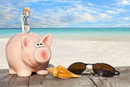 Piggy bank with banknotes, Seashells and Sunglasses on Wooden Baords at the beach with much Copy Space for additional information