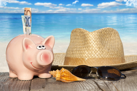 Piggy bank with banknotes, Seashells, Straw Hat and Sunglasses on Wooden Baords at the beach with much Copy Space for additional information