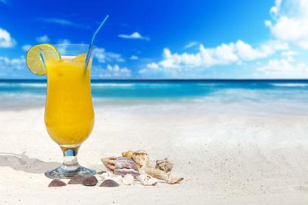 drinking straw: Cocktail di frutta con Orange e Cannuccia sulla spiaggia con alcune conchiglie e altro spazio della copia