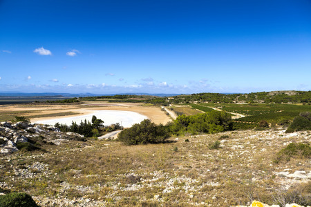 brine: Dried brine pool under bright blue sky at Gruissan in southern France