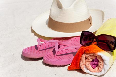 vacanza al mare: Accessori come occhiali da sole, telo mare, cappello di paglia e infradito per la spiaggia di vacanza