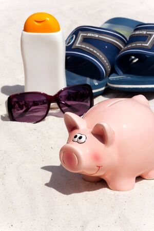 holiday budget: Piggy bank and beach accessories, saving for the next holiday Stock Photo