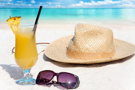 drinking straw: Cocktail di ananas con cannuccia e un cappello di paglia sulla spiaggia di sabbia tropicale