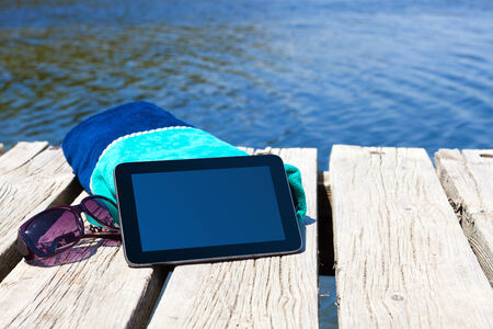 With a Tablet PC and beach towel on a swimming dock on the lake photo