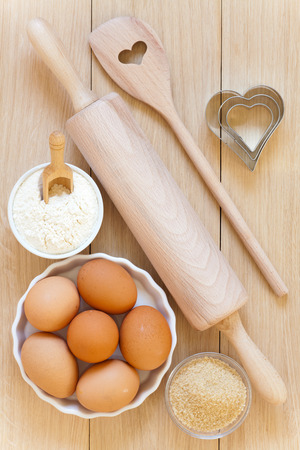 Baking utensils made of wood, eggs,flour and sugar in bowls on a wooden table Stock Photo